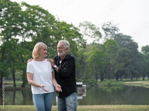 Leinwandbild Motiv A happy senior couple stand in a park on a sunny day. Relax in the forest spring summer time. free time, lifestyle retirement grandparents concept