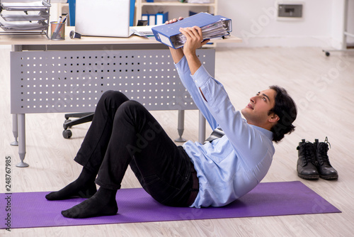 Young handsome male employee doing exercises in the office © Elnur