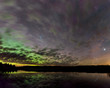 Aurora, stars and clouds reflecting in a calm lake