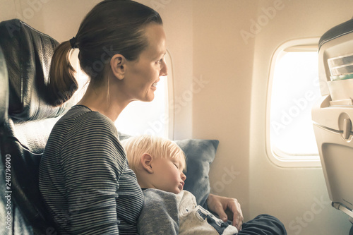 Leinwanddruck Bild  Happy mother traveling on airplane with her baby boy.