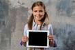 Leinwandbild Motiv Smiling blonde girl holding ipad in her hands and looking at the camera. - Horizontal image mockup