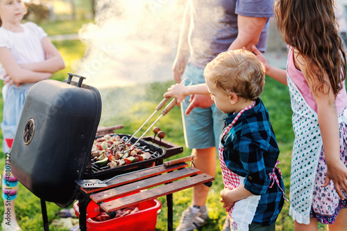 Little chef with apron grilling meat and vegetables on sticks. Next to him his cousins. Family gathering concept. - 248807322