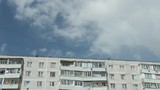 Timelapse of former clouds in the blue sky, floating on the background of an apartment building. Concept of poverty and poverty of ordinary Russian citizens - 248808303