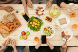 Enjoying dinner with friends.  Top view of group of people having dinner together while sitting at wooden table - 248825713