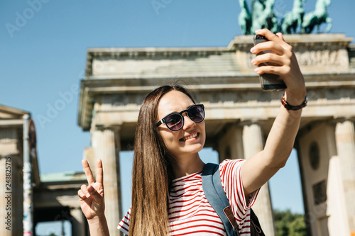 Leinwandbild Motiv Young beautiful positive girl makes selfie against the background of the Brandenburg Gate in Berlin in Germany or takes pictures of sights.
