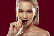 Close up of beautiful dark-eyed woman eating some chocolate