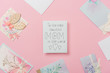 """white greeting card for mothers day with """"to the most beautiful mom in the world"""" handwritten text and hearts, and various postcards arranged around on pink background"""