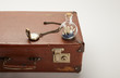 toy ship in glass bottle and compass on brown suitcase with copy space