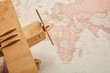 close up of toy wooden plane on world map