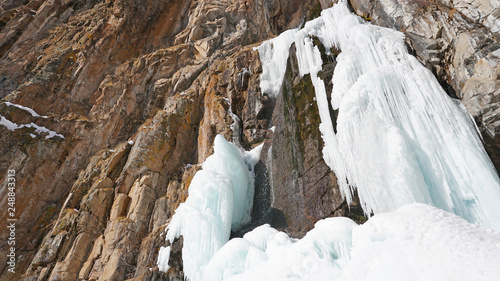 Frozen waterfall among the rocks. The waterfall is freezing, huge icicles. Ice white and blue. Brown rocks and splashes of water. Winter waterfall. White snow and blue sky. Water runs down the ice. - 248843313