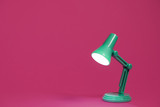 Retro green desk lamp on a bright pink background.  Landscape orientation with a right side composition with copy space and room for text. - 248847356