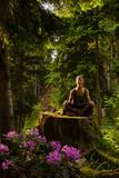 una donna fa yoga nella natura bosco meditazione