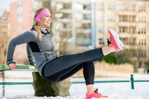 Woman stretching her limbs for sports exercise in winter