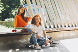 Two girls dressed in the style of 80s hippie pose in the park - 248884105
