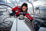 Young sailor guy sets sail on a boat. - 248884126