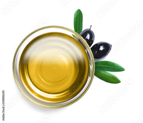 Leinwanddruck Bild Glass bowl with olive oil with leaves on white
