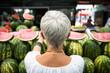 Quadro Senior woman buying watermelon on market