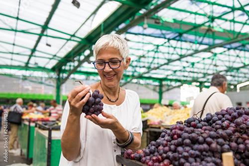 Senior woman buying grape on market