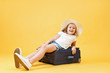 A little blonde kid girl dreams of traveling and lies on a suitcase. Yellow background