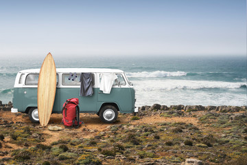 Tourist camp with bags, surfboard and car on the ocean
