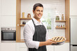Young man with a pie in a modern kitchen