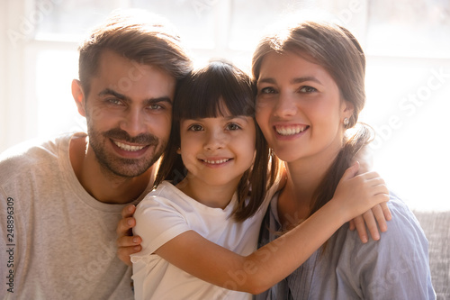 Leinwandbild Motiv Happy mom dad and little daughter with smiling faces portrait