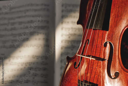 Leinwanddruck Bild Preparing for a concert. Classic brown violin on music score sheet background. Musical instruments.