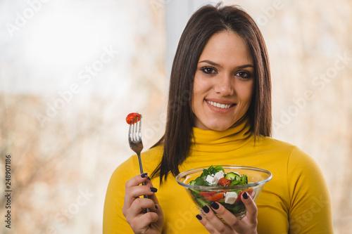 beautiful woman holding salad and looking at camera