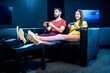 Young couple playing video games with gaming console sitting on the couch in the dark room of the playing club