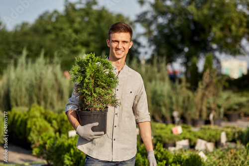 Leinwanddruck Bild Guy gardener holds in his hand a pot with plant in the wonderful nursery-garden on a warm sunny day