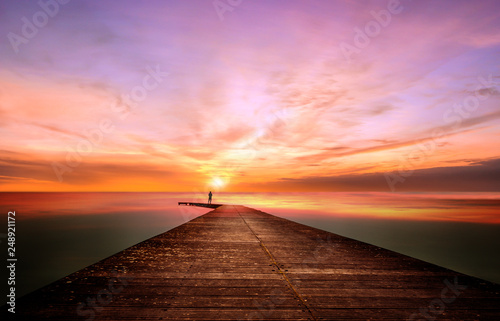 A person on a pier observes and contemplates a splendid sunset © magati