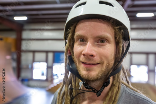 Leinwanddruck Bild Portrait of a man with dredlocks and a helmet at an extreme sports park
