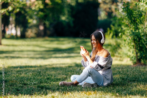 Young woman listens to music via headphones and smartphone in the park