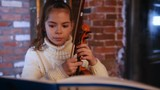 Musical lesson. A little girl put notes on the stand and start playing violin - 248930356
