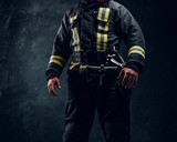 Cropped image of a fireman wearing full protective equipment on black background in studio