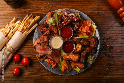 meat plate with souses and tomato and paper decorated  - 248936527