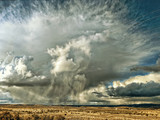 High wire powerlines slice across stormy rain clouds in southeastern Oregon. - 248942710