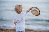 A rear view of small toddler boy with hat standing on beach on summer holiday. - 248943762