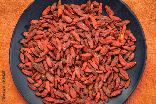 dried goji berries on am black plate - 248952191