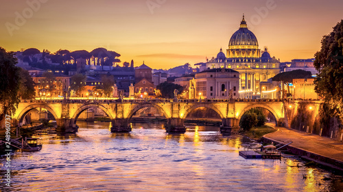 Leinwanddruck Bild The dome of Saint Peters Basilica and Vatican City at sunset. Sant'Angelo Bridge over the Tiber River. Rome, Italy