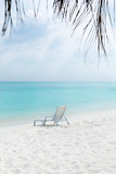 Sun chair on sandy beach at tropical vacation,