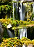 waterfall splashing on mossy rocks below