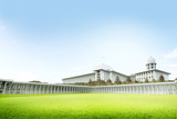 Majestic mosque in Jakarta with green grass field and blue sky background