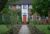 large brick house with shady English garden - 248999736