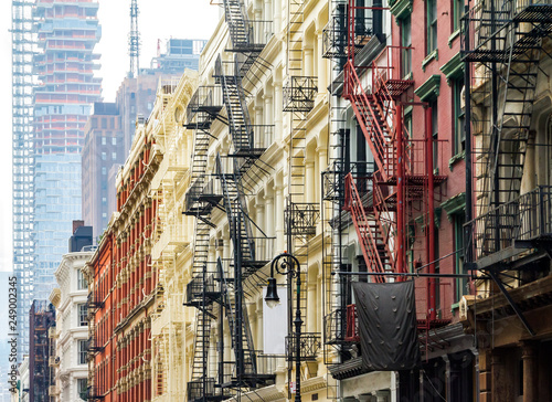 Foto Murales Old historic buildings along Greene Street in SoHo Manhattan contrast against the modern tower in the background Manhattan skyline in New York City