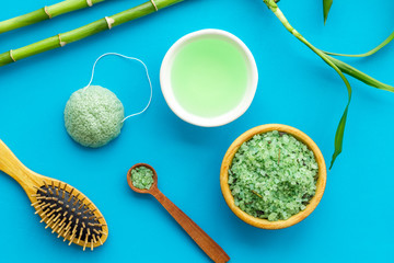 Asian spa treatment concept with natural ingredients. Spa salt, lotion, sponge near bamboo on blue background top view