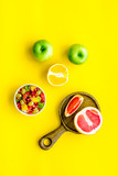 Healthy diet concept. Fruit salad near fresh fruits on yellow background top view