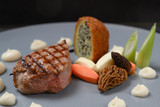 festive menu dish with roasted veal, morels, vegetables and a fried potato stuffed with onion seeds on a blue gray plate - 249018791