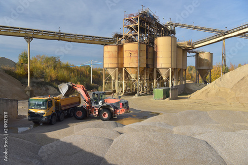 Leinwanddruck Bild Radlader belädt LKW mit Sand in einem Kieswerk // Wheel loader loads truck with sand in a gravel plant