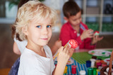 Portrait of smiling boy painting easter eggs - 249034789